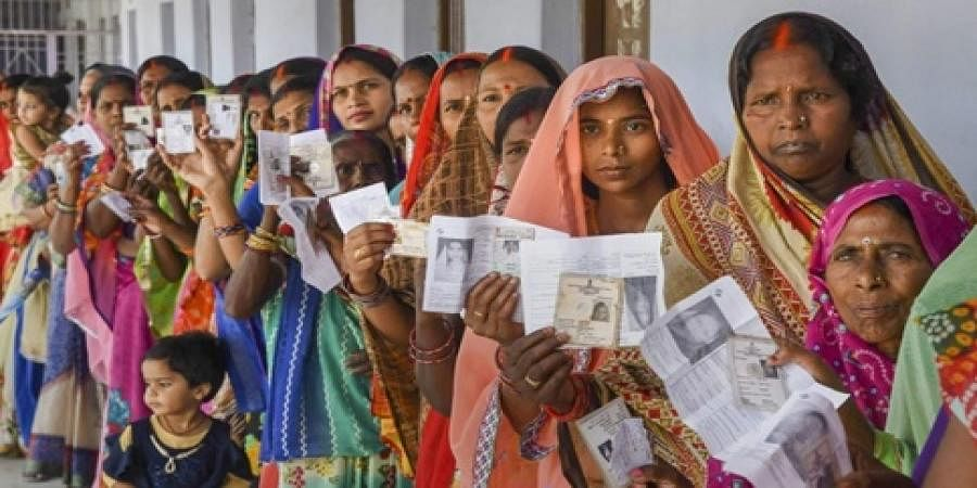 Women show their voter identity cards as they stand in a queue at a polling station.