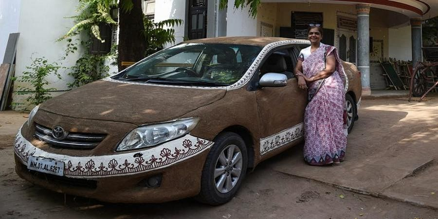 woman plasters her car with bovine DUNG