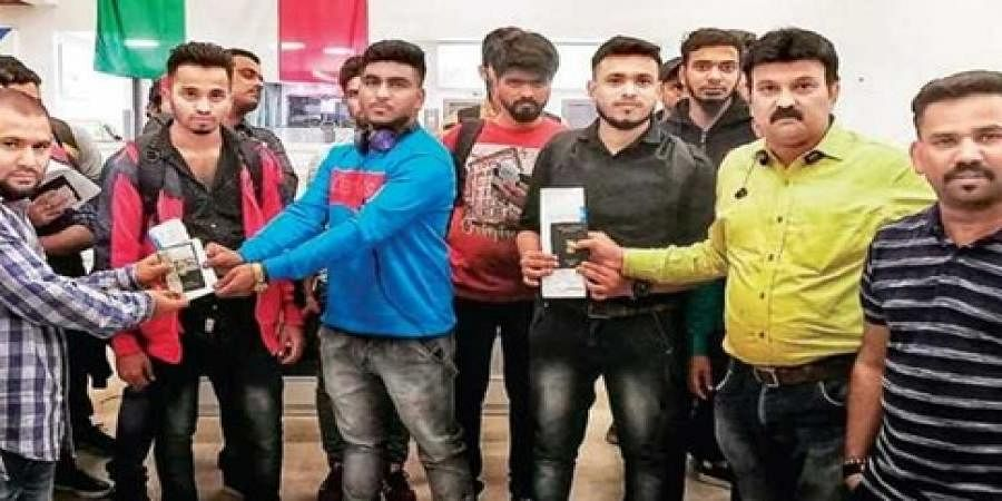 Indian expats hand over passports and tickets to Mangaloreans, who had become victims of the job fraud, at Kuwait airport