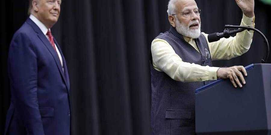 President Donald Trump listens as India Prime Minister Narendra Modi speaks during the 'Howdy Modi' event.