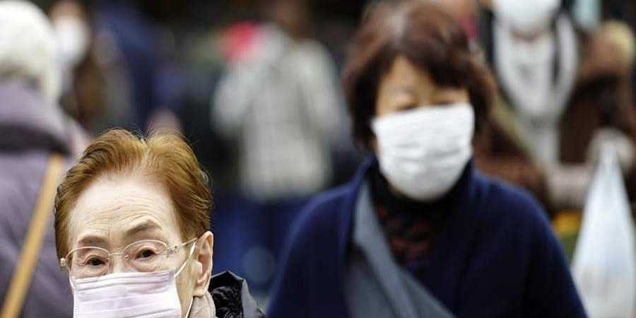 Pedestrians_wear_protective_masks_as_they_walk_through_a_shopping_district_in_Tokyo1