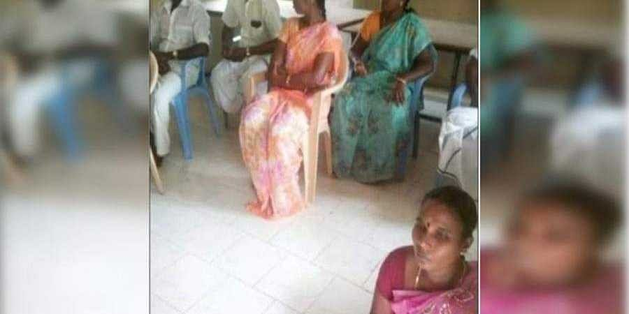 S Rajeswari (in pink) was sitting on the floor at a meeting and others were sitting on chairs.