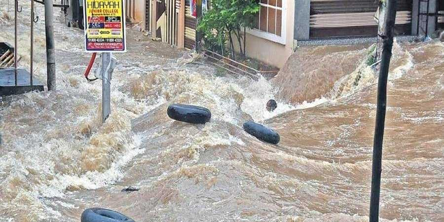 A man tries to hold on to a tyre to save himself from getting washed away in Falaknuma on Wednesday. He is yet to be traced