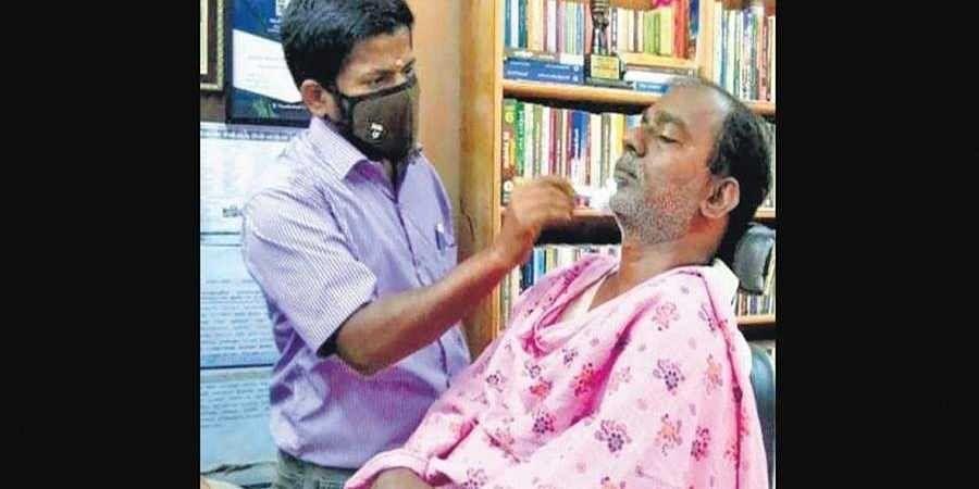 P Pon Mariappan at work in his salon cum library in Millerpuram.