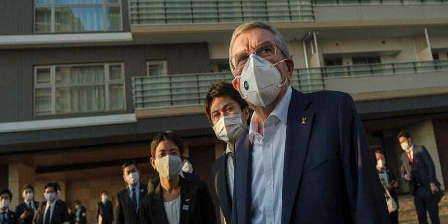 IOC President Thomas Bach wearing a protective mask visits the Olympic and Paralympic Village in Tokyo.