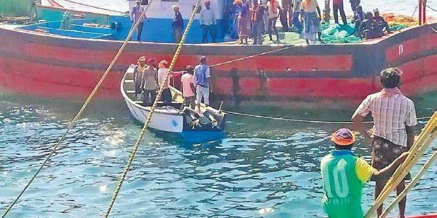 Boats look for the missing fishermen whose vessel capsized in the Arabian Sea.
