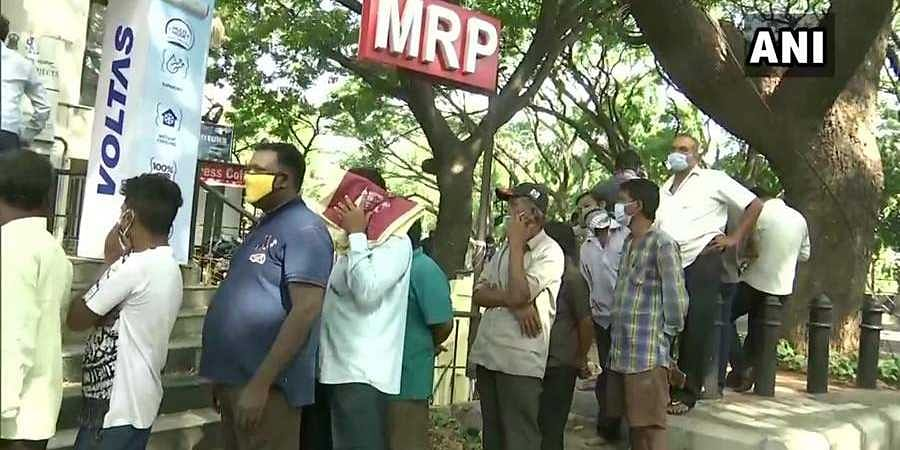 People line up at a liquor shop in Bengaluru