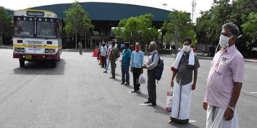 Passengers maintain social distance while boarding a bus to Tirumala at