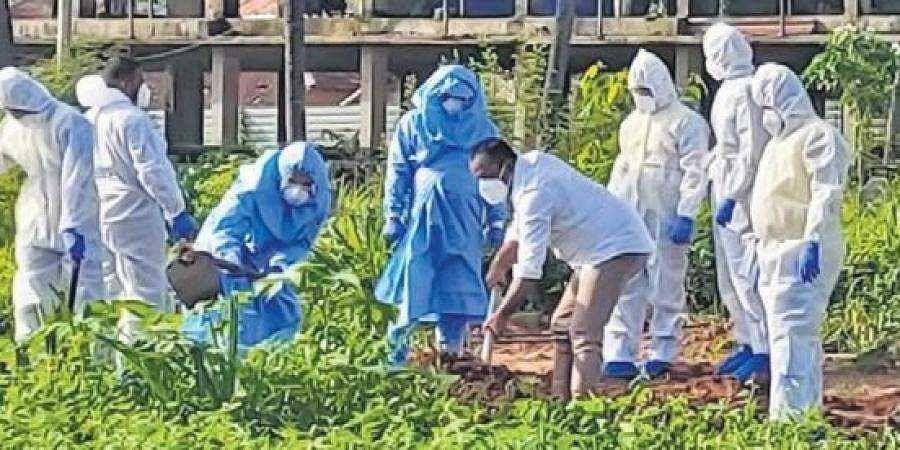 Mangaluru MLA U T Khader helps bury a victim of Covid-19 along with health workers, in Mangaluru on Wednesday