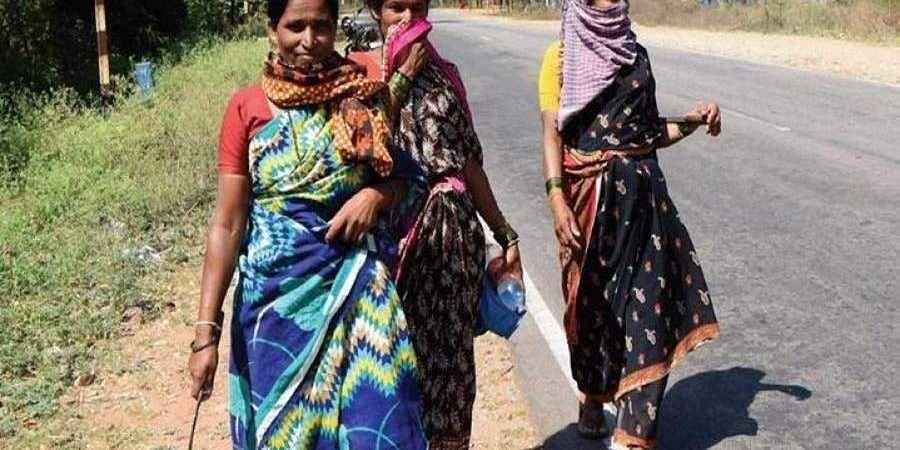 Labourers walk on the roads of HD Kote taluk