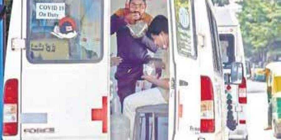 Ambulance staffers on Covid-19 duty grab a bite as they wait near a testing centre on JC Road, Bengaluru