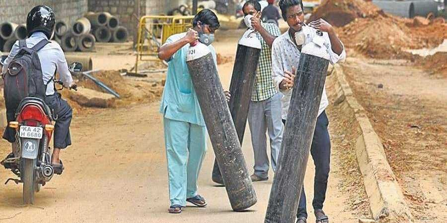 Employees of a private hospital forced to carry oxygen tanks on Dickenson Road in Bengaluru, which has been dug up