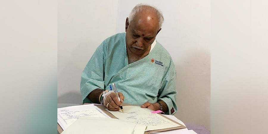 Chief Minister Yediyurappa signs on files from his hospital suite
