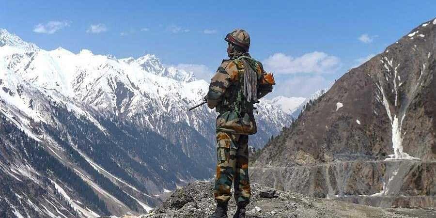 Army jawan stands guard as a militar convoy passes through Ladakh
