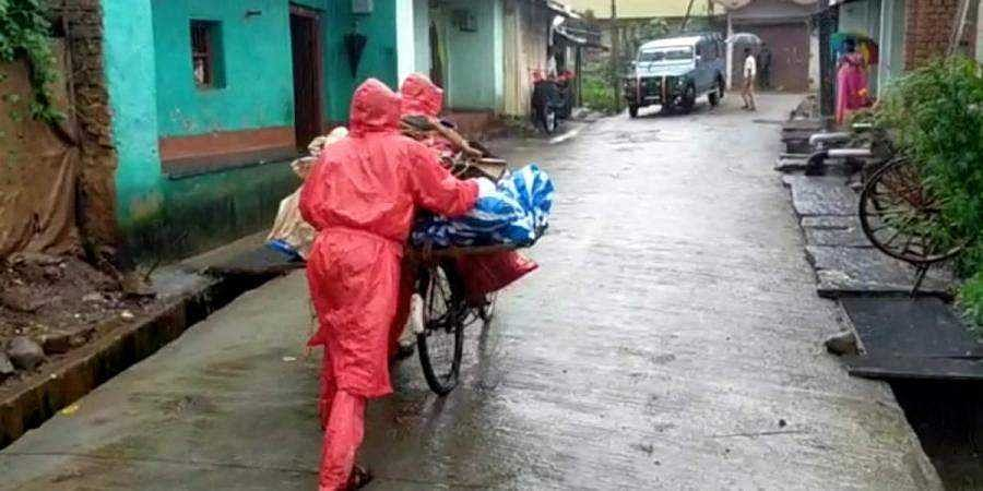 Family members carrying the dead body to crematorium using a bicycle.