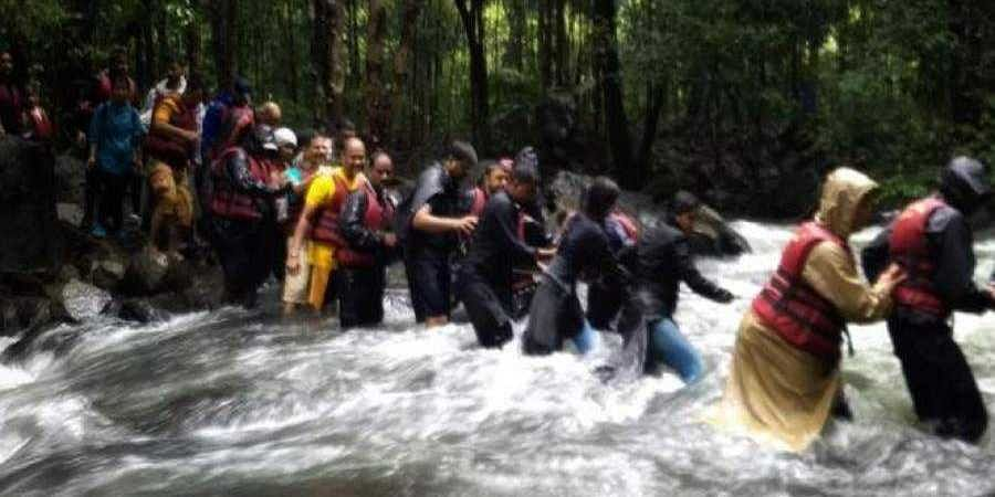 Trekkers cross a gushing stream while trekking to Dudhsagar