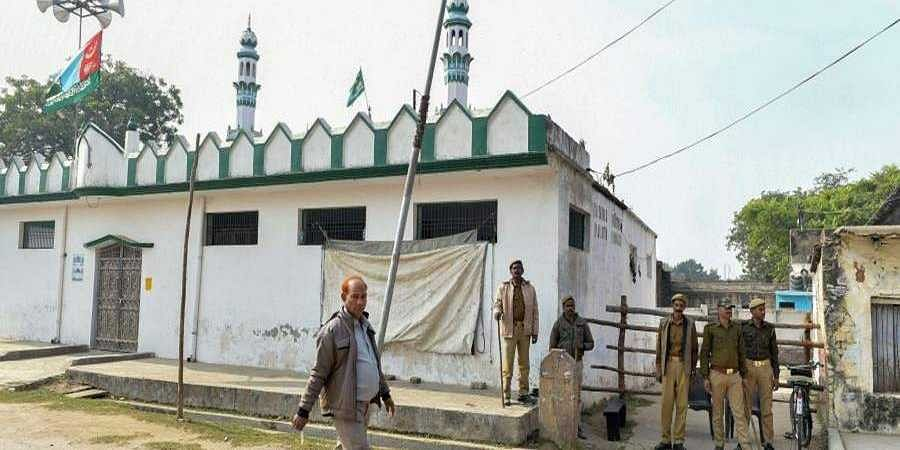 Policemen stand guard outside Terhi Bazaar Masjid on the eve of the 27th anniversary of the Babri Masjid demolition in Ayodhya Thursday Dec. 5 2019.