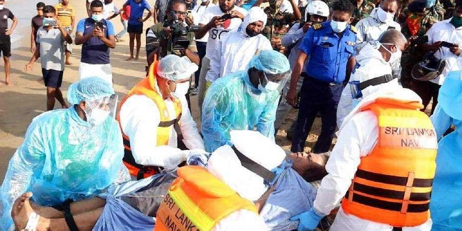 An injured crew member of the MT New Diamond, is transferred on stretcher to an ambulance Thursday, Sept. 3, 2020, in Sangamankanda, Sri Lanka