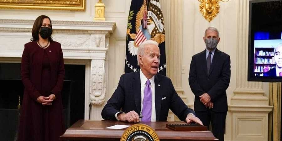 US President Joe Biden responds to a reporters question after signing executive orders in the State Dinning Room of the White House, Thursday, Jan. 21, 2021, in Washington DC