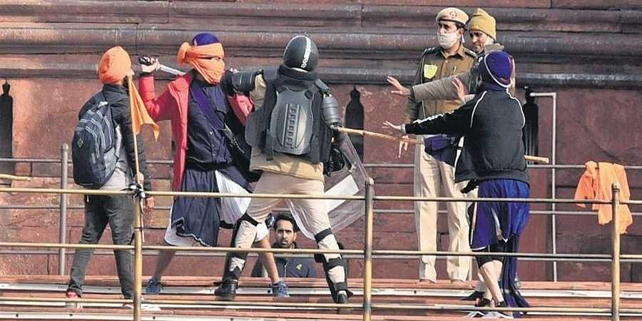 Protesters and police personnel clash at the ramparts of the Red Fort in New Delhi on Tuesday