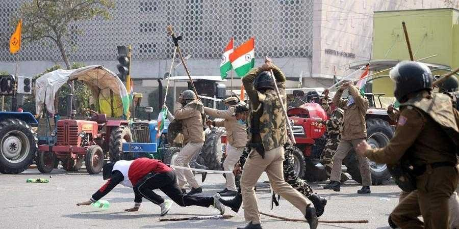 Police personnel start lathi-charge on protesting farmers at ITO during the tractor rally on Republic Day.