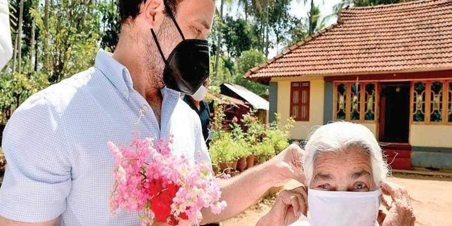 Rahul Gandhi helps Anna Mathai put on her facemask in front of her house near Poothadi in Wayanad on Monday