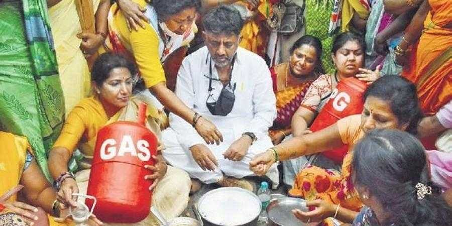 KPCC president D K Shivakumar and members of Mahila Congress stage a protest against the LPG and fuel price hike at Sangoli Rayanna Circle, in Bengaluru on Tuesday