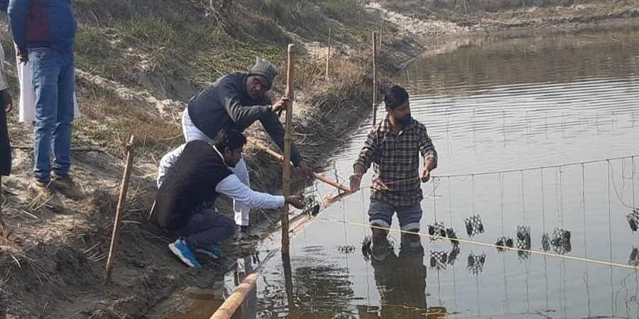 Nitil Bhardwaj with his employees at a pond meant for pearl farming