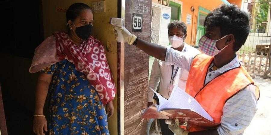A_healthcare_worker_conducts_thermal_screening_on_a_woman1