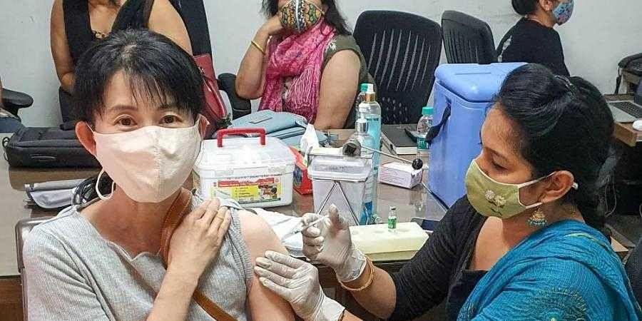A medic administers the COVID-19 vaccine dose to a Japanese woman during a vaccination drive at IMT Industrial Association office, at Manesar in Gurugram district. (Photo | PTI)