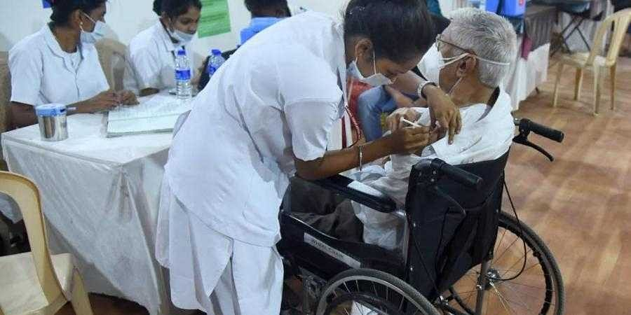 A medic vaccinates a person with a physical diaability during an inoculation drive, as coronavirus cases surge in Mumbai. (Photo | PTI)