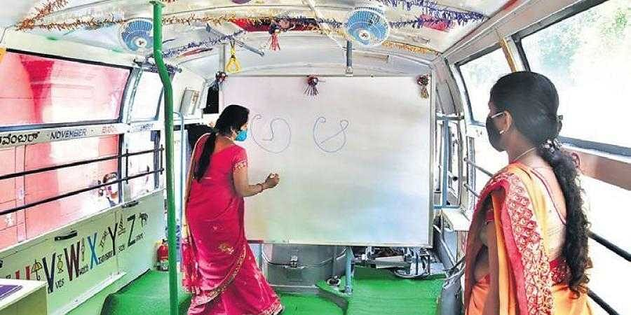 A woman gives a demonstration inside one of the mobile school buses that was launched in Bengaluru on Saturday