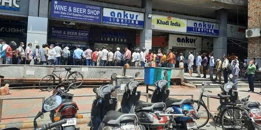People gather in large numbers outside a liquor shop in Khan Market