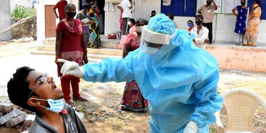 A health worker collects swab samples for Covid-19 test, at a ward secretariat in Tirupati. (Photo | Madhav K, EPS)