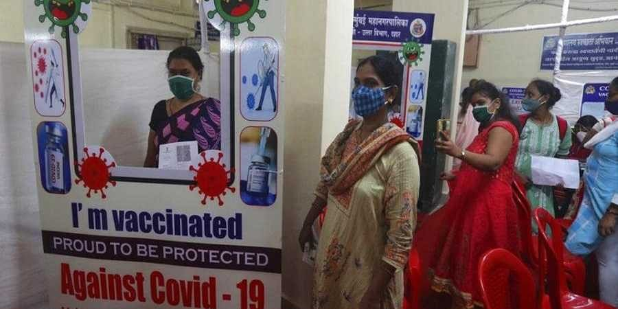 A woman gets a photograph after being administered the COVISHIELD vaccine for COVID-19 at a vaccination centre in Dharavi, Mumbai.
