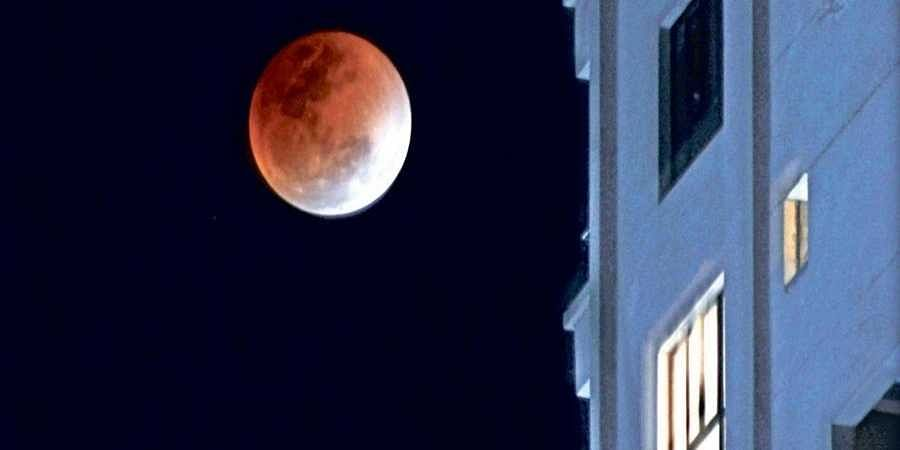 Supermoon rises behind a building in Bhubaneswar
