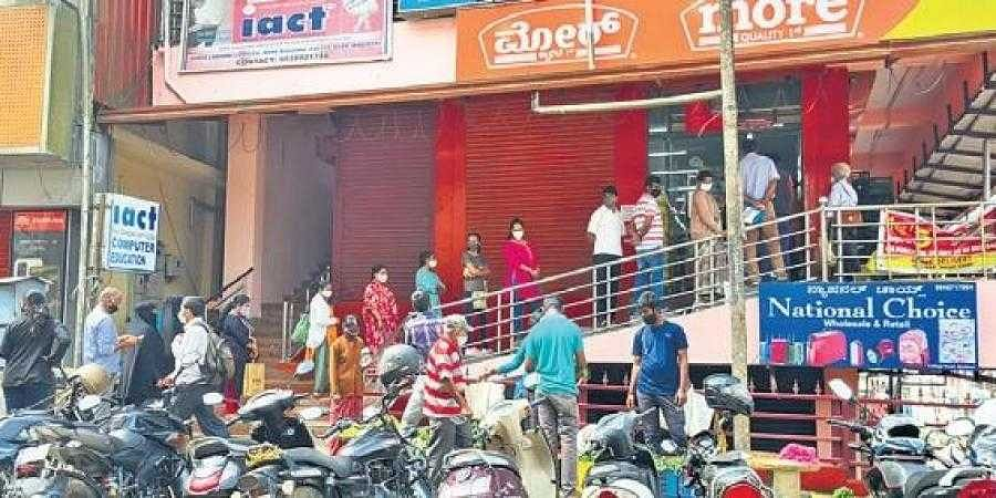 People crowd outside shops in Madikeri during curfew relaxation on Tuesday