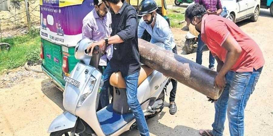 As Bengaluru's demand for oxygen peaks, a group of people are seen trying to transport an oxygen cylinder on a two-wheeler, in Bengaluru on Tuesday